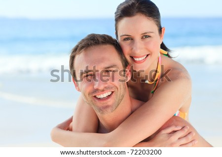 Man having wife a piggyback on the beach - stock photo