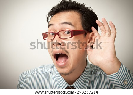 man hearing with hand on ear isolated on a white background. - stock photo