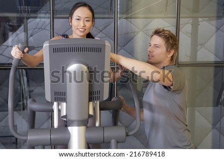 Man helping a woman in the gym.