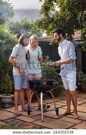 man helping at the outdoor garden barbeque with a plate while man serves healthy chicken meat - stock photo