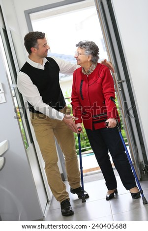 Man helping elderly woman with crutches - stock photo