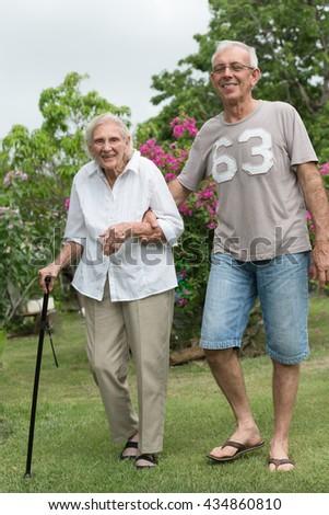 Man helping happy senior lady walking in garden - stock photo