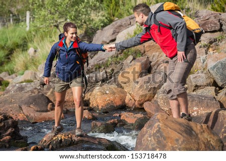 Man helping his smiling girlfriend to cross a river on a hike