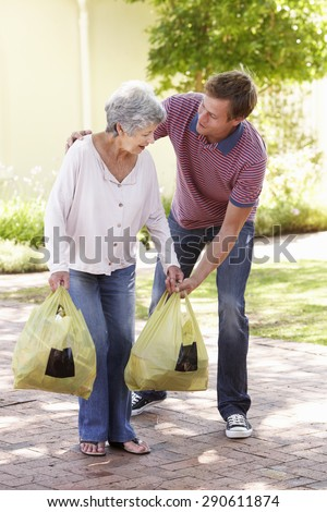 Man Helping Senior Woman With Shopping - stock photo