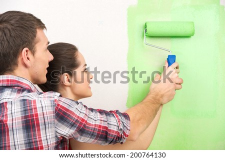man helping woman paint wall. beautiful couple holding painting roller together - stock photo