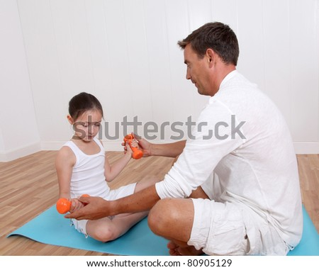 Man helping young girl with fitness exercises - stock photo