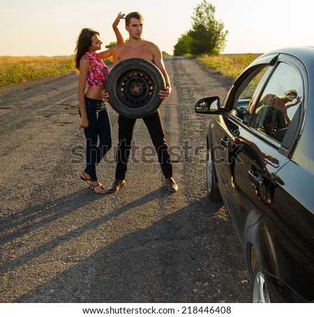 man helps a woman to replace the wheel on the car - stock photo