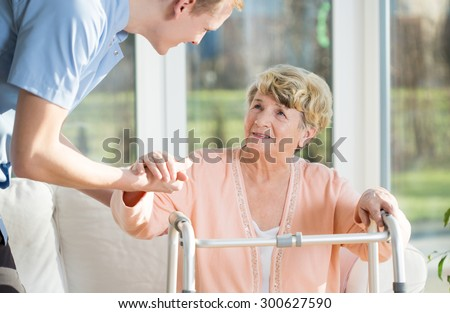 Man helps to stand up an older woman at nursing home - stock photo
