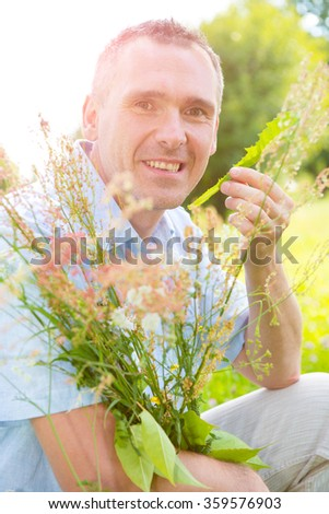 Man herbalist picking up wild herbs