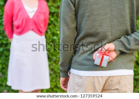 man hide silver with red ribbon gift box on his back with women in background - stock photo