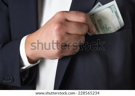 Man hides a bribe into a pocket of his blue jacket  - stock photo