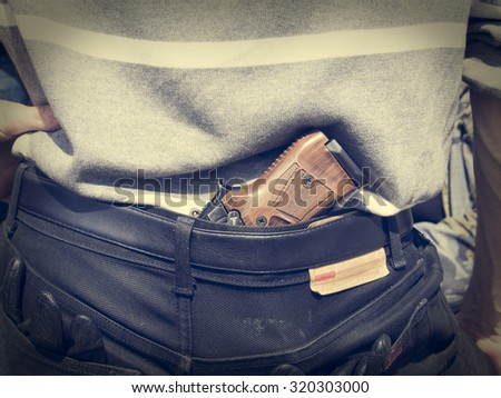 man hides a pistol behind his back under the belt of jeans - stock photo