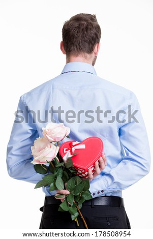 Man hiding a flower behind his back isolated on white background. - stock photo