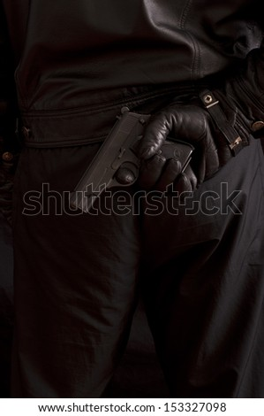 Man hiding a gun behind his back - stock photo