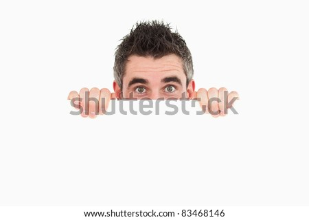 Man hiding behind a copy space against a white background - stock photo