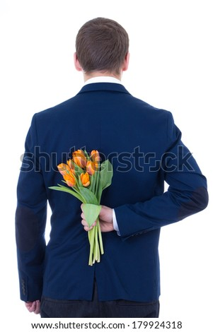 man hiding bouquet of flowers behind his back isolated on white background - stock photo