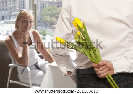 Man hiding bouquet of flowers tulip behind his back - stock photo