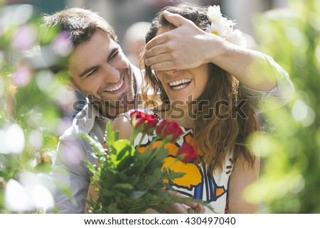 Man hiding his girlfriend to offer her a bouquet - stock photo