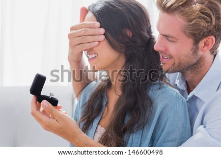Man hiding his wifes eyes to offer her an engagement ring for a marriage proposal - stock photo