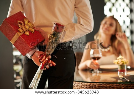 Man hiding red rose and gift for his girlfriend behind his back - stock photo