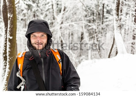 Man hiker hiking in white winter forest with backpack. Recreation and healthy lifestyle outdoors in snowy nature. Young male looking at camera and smiling. - stock photo
