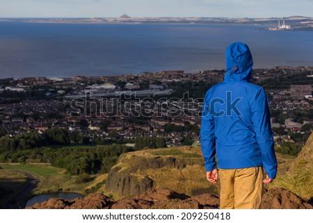 Man hiker is leaving city behind - stock photo