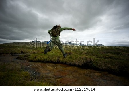 Man hiker jumping across small river - stock photo