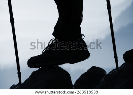Man hiker legs in boots and poles stand on mountain peak rock - stock photo