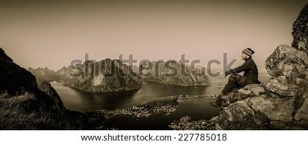 Man hiker looking at Reine village panorama, Norway - stock photo