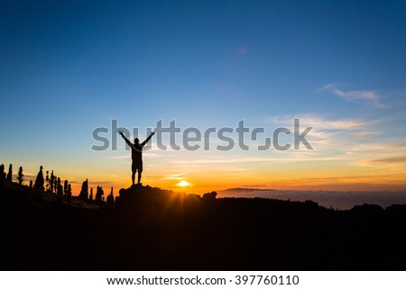 Man hiker silhouette with arms outstretched in mountains. Male runner or climber looking at sunset view. Business concept and hands up and enjoy inspirational landscape on Tenerife, Canary Islands - stock photo