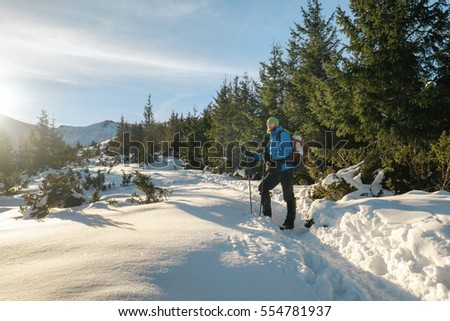 Man hiker stand on the mountain trail with trekking sticks and enjoying winter landscape