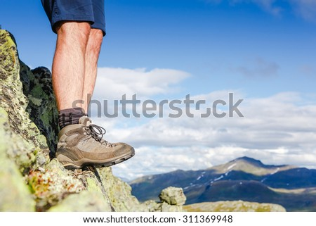 man hiker stand on the rocky mountains - stock photo