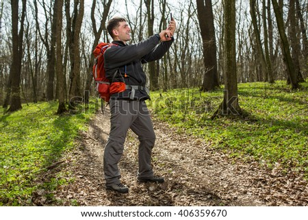 Man hiker taking photo with smart phone in forest