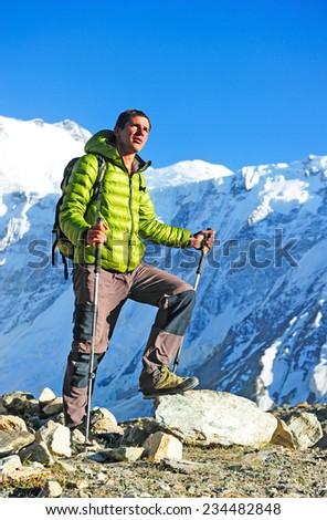 Man hiker trekking in high Himalaya Mountains in Nepal - stock photo