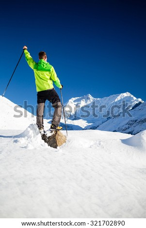 Man hiker trekking in high Himalaya Mountains in Nepal. Happy hiking climbing in white winter or autumn beautiful inspirational landscape. Annapurna peak in background. - stock photo