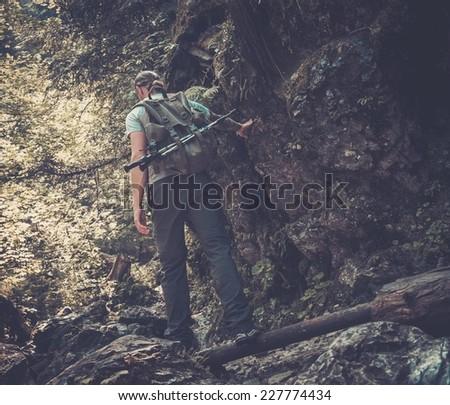 Man hiker walking across stream in mountain forest - stock photo