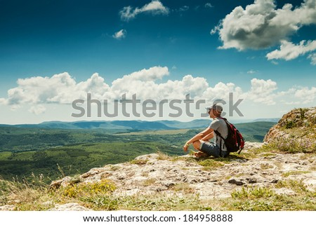 Man hiker with backpack relaxing on top of a mountain - stock photo