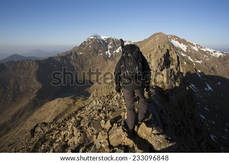 man hiking across rocky mountain ridge in north wales on a sunny day - stock photo