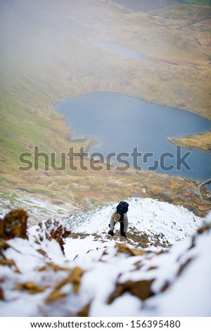 Man hiking in Snowdonia at winter, Crib Goch Mountain. Snowdonia National Park, North Wales, England, United Kingdom, Great Britain, UK, Eng, GB, Europe.