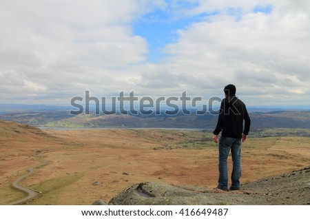 Man hiking in the English Lake District Cumbria. View across Torver Common towards Coniston Water.