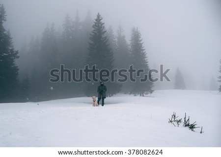 man hiking in the snowy mountains with labrador dog