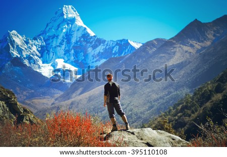 Man hiking on a stone   view in the himalayas,   Ama Dablam ,Nepal - stock photo