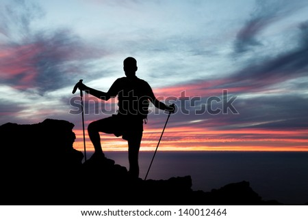 Man hiking silhouette in mountains, sunset and ocean. Male hiker with walking sticks on top of mountain looking at beautiful night landscape.