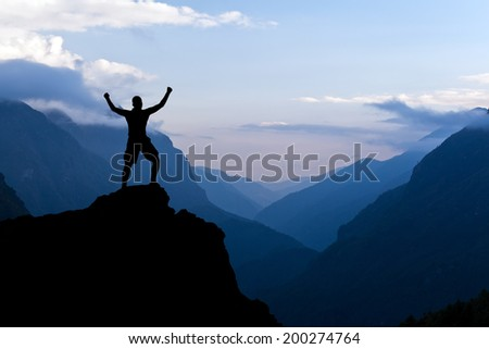 Man hiking success silhouette in mountains. Male hiker with arms outstretched on top of mountain looking at beautiful Himalayan landscape. - stock photo