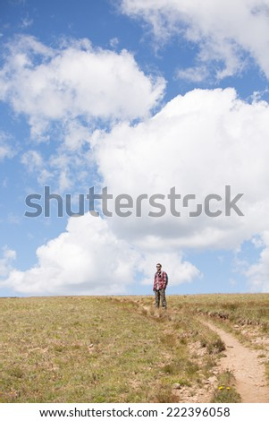Man Hiking - This is a shot of a young man enjoying a hike on a beautiful summer afternoon. - stock photo