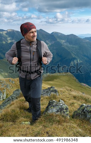 Man hiking with backpack into the mountains