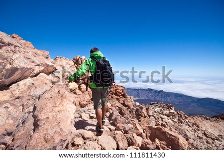 Man hiking. Young  guy hiking / backpacking in the rough  volcanic landscape on the volcano, Teide, highest peak of Spain. - stock photo