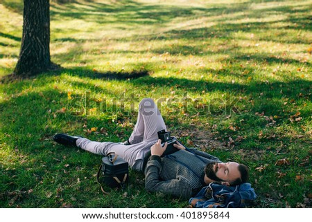 man hipster photographer  with old film camera medium format lying on the grass and dream and relax