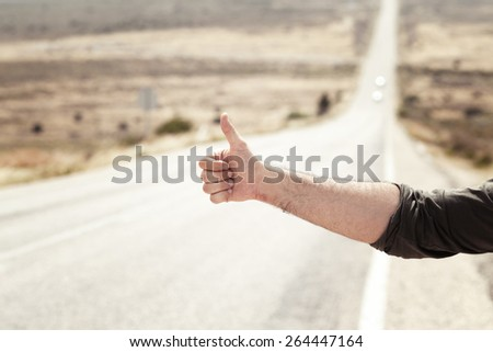 Man Hitchhiking on a Country Road - stock photo