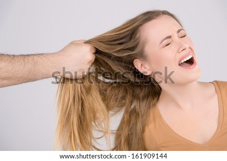 Man hitting a young woman. Close up of hand pulling female hair  - stock photo